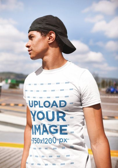 T-Shirt Mockup of a Man Standing in a Parking Lot on a Sunny Day 22400