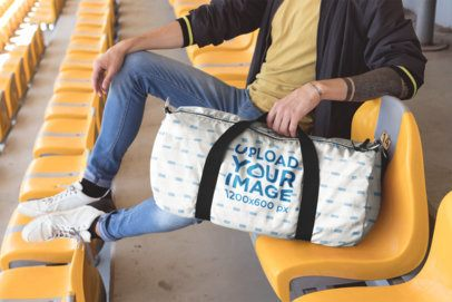 Mockup of a Duffle Bag Featuring a Man Sitting in Stadium Seats 23246