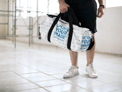 Mockup of a Man Carrying a Duffel Bag at a Hallway 23058