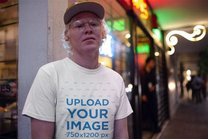 Round Neck Tee Mockup of a Man Outside a Store with Neon Signs at Night 22246