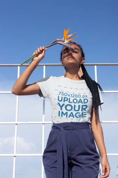 T-Shirt Mockup of a Girl with Braids Holding a Bird-of-Paradise Flower 21806