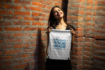 Mockup of a Happy Young Woman Showing Off Her Cool Drawstring Bag 23669