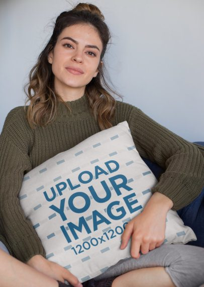 Mockup of a Woman Holding a Square Pillow While Sitting 23577