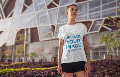 T-Shirt Mockup of a Woman with a Buzz Cut Hairstyle Standing in Front of a Modern Building 20176