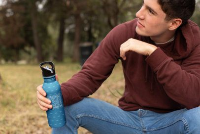 Mockup of a Man Holding His Aluminum Water Bottle in a Meadow 24441
