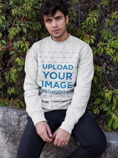 Crewneck Sweater Mockup Featuring a Man with Curly Hair Sitting Against Plants 18194