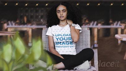 Parallax Video of a Girl with Kinky Hair Sitting in a Relaxing Area Wearing a Crew Neck T-Shirt 26328