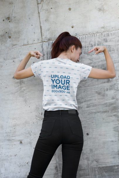 Back View T-Shirt Mockup of a Woman Raising Her Arms Against a Concrete Wall 24977