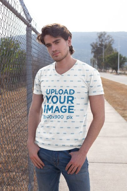 Mockup of a Man with a Sublimated V-Neck T-Shirt Standing by a Chain Link Fence Gate 24989