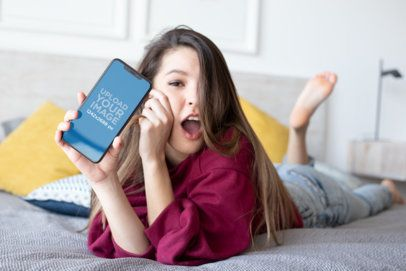 iPhone XS Max Mockup of an Amazed Girl Lying on Her Bed 25833