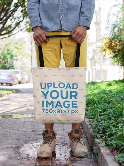 Mockup of a Man with Distressed Shoes Holding a Tote Bag on a Street Puddle 26710