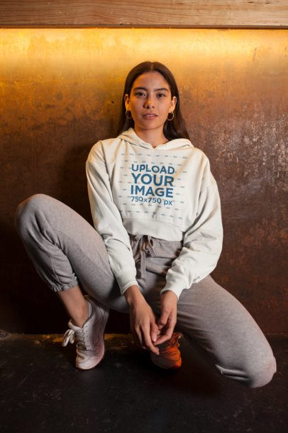 Crop Top Hoodie Mockup of a Woman with Hoop Earrings Kneeling at a Bar 26102