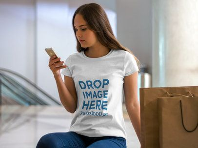 T-Shirt Mockup of a Woman Using her iPhone at a Mall a7977