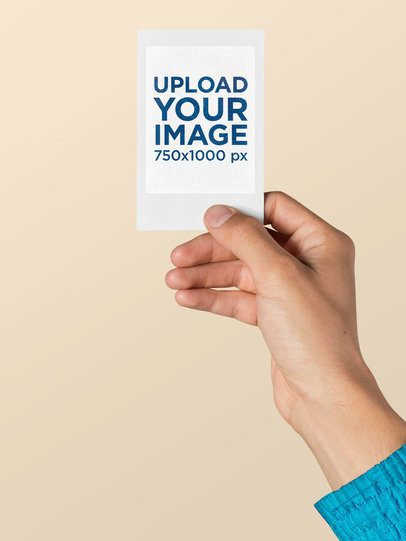 Mockup of a Blue Jacket Person Holding an Instax Picture Frame 26173
