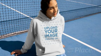 Hoodie Video Featuring a Woman Sitting in a Tennis Court 13210