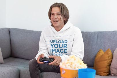 Pullover Hoodie Mockup of a Joyful Gamer Man Playing Video Games on a Couch 26904