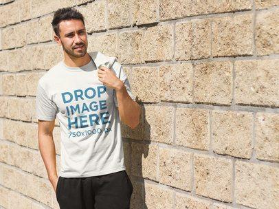 Young Man Standing Next to a Brick Wall T-Shirt Mockup a8018