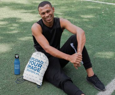 Drawstring Bag Mockup of an Athletic Guy in a Soccer Field 27579