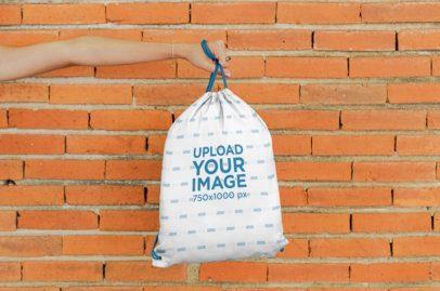 Mockup of a Hand Holding a Drawstring Bag Against a Brick Wall 27574