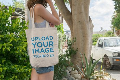 Tote Bag Mockup Featuring a Woman with Denim Shorts Against a Tree 11-el