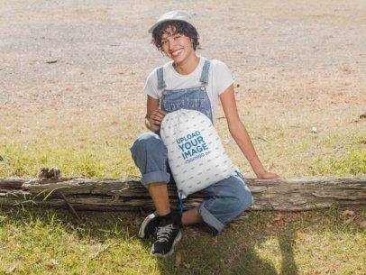Drawstring Bag Mockup of a Woman Sitting on a Wood Log at the Countryside 27595
