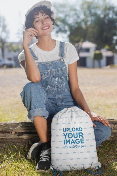 Drawstring Bag Mockup of a Happy Woman Sitting on a Wood Log 27596