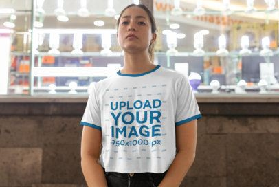 Mockup of a Woman Wearing a Ringer T-Shirt Against a Lightbulb Window Display 27158