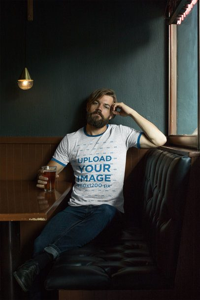Mockup of a Bearded Man Wearing a Ringer Heathered T-Shirt Sitting on a Restaurant Couch 27928
