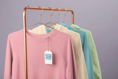 Clothing Tag Mockup Featuring a Rack of Crewneck Sweatshirts 27666