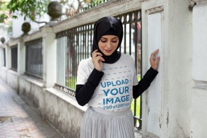 T-Shirt Mockup Featuring a Woman With a Hijab Walking on a Sidewalk 28295
