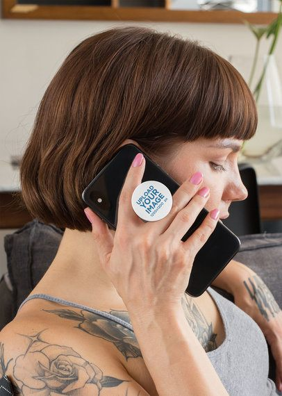 Phone Grip Mockup Featuring a Woman With Tattoos Sitting on a Couch 28155