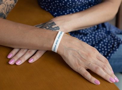 Mockup of a Tattooed Woman Wearing a Silicone Wristband 28224