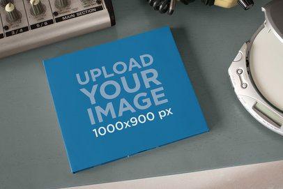 Mockup of a Digipak on a Desktop Next to a CD Player 28347