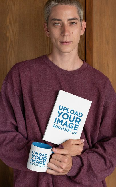 Mockup of a Young Man Holding a Book and a Two-Toned Coffee Mug 28457