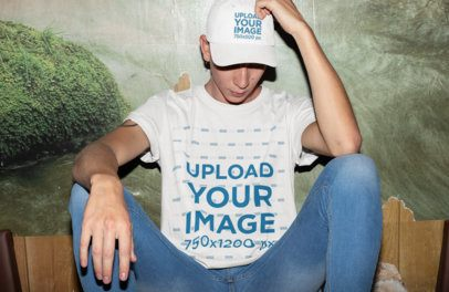 T-Shirt Mockup of a Man Wearing a Dad Hat Sitting Against a Wall 28581