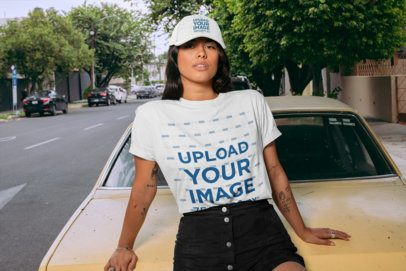 T-Shirt Mockup of a Woman with a Dad Hat Sitting on an Old Car 28607