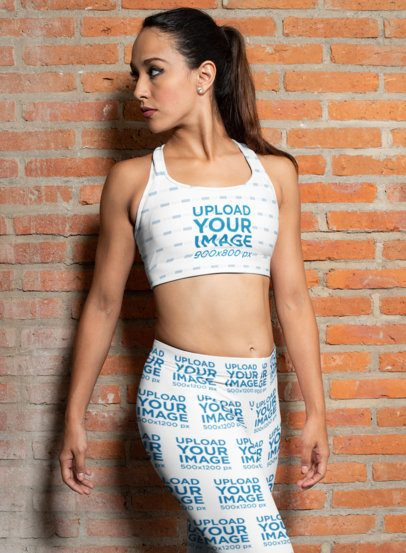 Mockup of a Woman Wearing a Sports Bra and Leggings Against a Brick Wall 28685