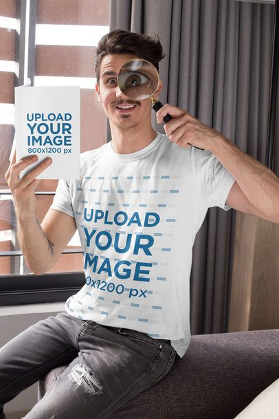 T-Shirt Mockup of a Man Playing with a Magnifying Glass while Holding a Book 28501