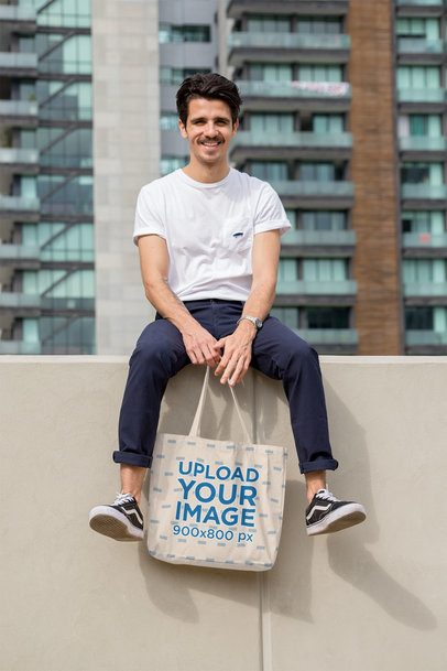 Tote Bag Mockup Featuring a Stylish Man Sitting on a Wall 28839