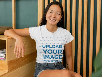 Mockup of a Woman with a Heather T-Shirt Sitting Against a Wooden Background 28752