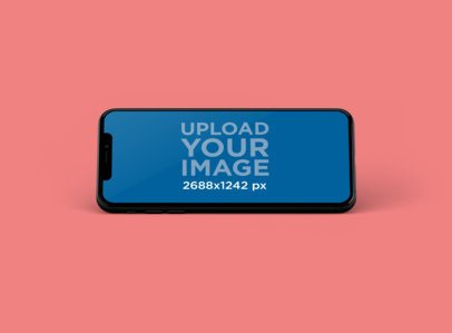 Mockup of an iPhone XS Max Leaned in Portrait Position at a Colored Spot 252-el
