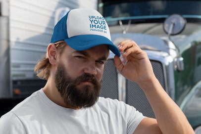 Mockup of a Bearded Man with a Trucker Hat Standing Next to a Truck 29488