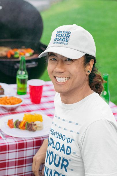 T-Shirt Mockup of a Smiling Man Wearing a Customizable Dad Hat at a BBQ Party 29719