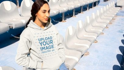 Hoodie Video of a Young Woman Sitting on a Stadium Bleachers 13209
