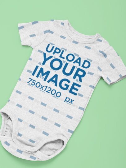 Heathered Mockup of a Short Sleeve Onesie Lying Flat on a Surface 29835