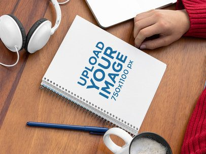 Spiral Notebook Mockup Placed over a Wooden Surface by Some Headphones 29946