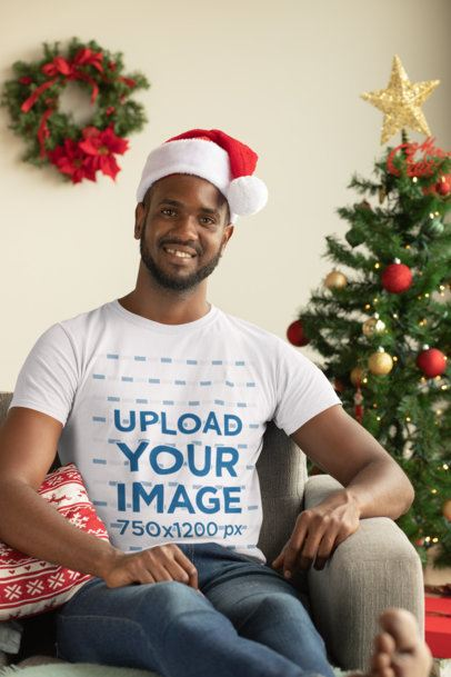 Mockup of a Man with a Crewneck T-Shirt Sitting Next to a Christmas Tree 30344