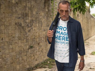 Elder Man Outdoors Wearing a T-Shirt and Carrying an Umbrella Mockup a10983