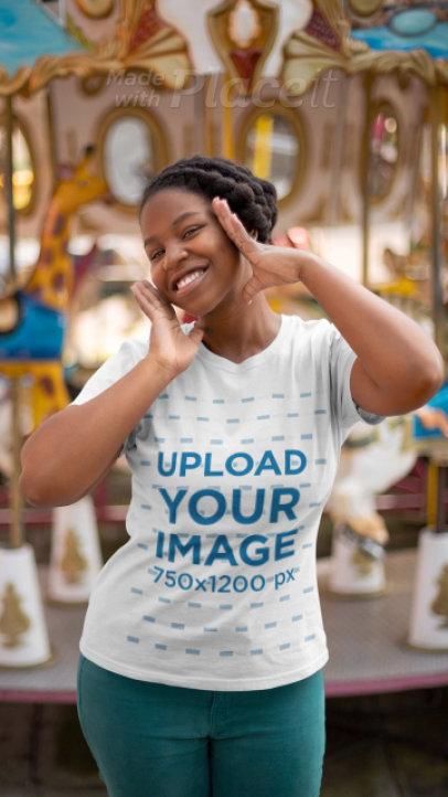 T-Shirt Video Featuring a Joyful Woman Posing by a Carousel 22991