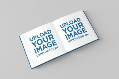 Mockup of a Square Hardcover Book Lying Open on a Solid Color Surface 1548-el